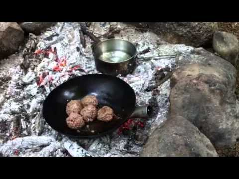 Campfire cooking meatballs in tomato sauce