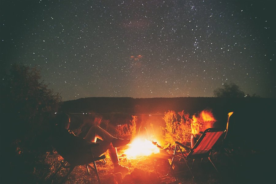 Two friends are sitting around a campfire